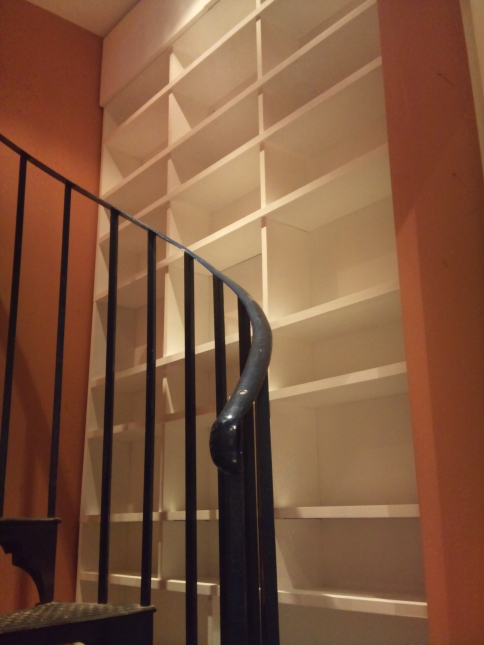 Shelving designed to make use of a stairwell around a spiral staircase. Finished in Farrow and Ball Wimbourne white