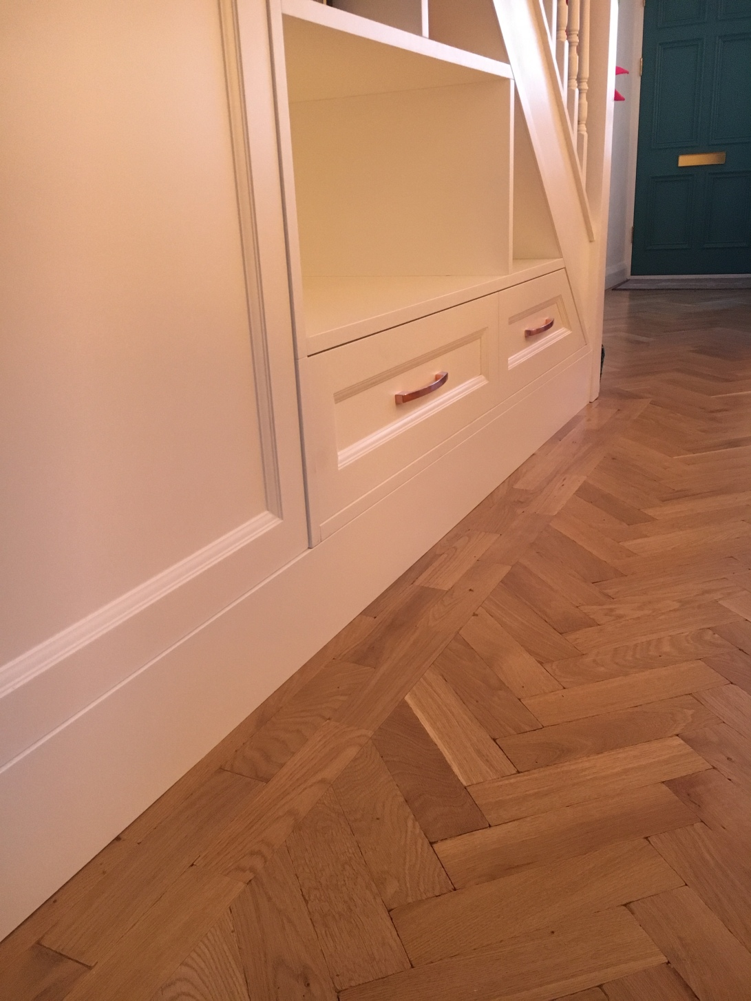 Under stair cupboards with brass handle detail on drawers